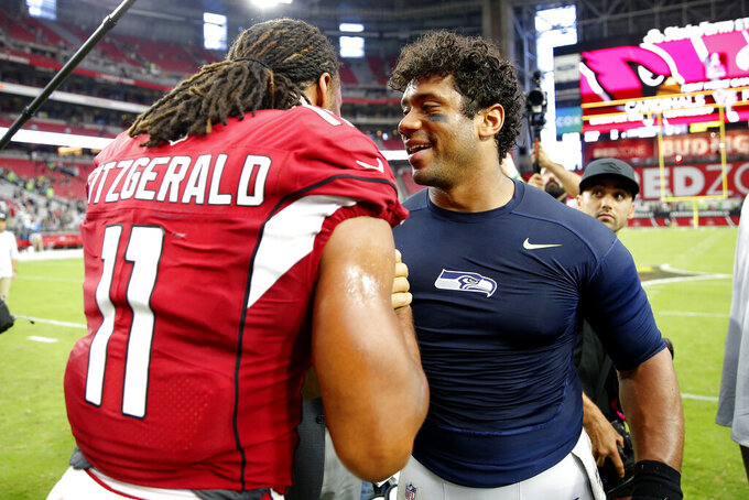 Arizona Cardinals wide receiver Larry Fitzgerald (11) greets Seattle Seahawks quarterback Russell Wilson after an NFL football game, Sunday, Sept. 29, 2019, in Glendale, Ariz. The Seahawks won 27-10. (AP Photo/Rick Scuteri)