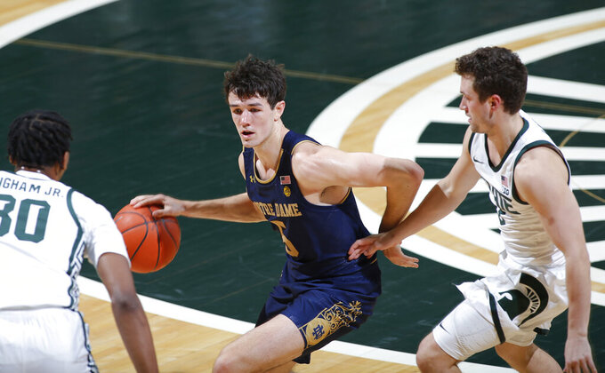 Notre Dame's Cormac Ryan, center, drives against Michigan State's Marcus Bingham Jr., left, and Foster Loyer, right, during the first half of an NCAA college basketball game, Saturday, Nov. 28, 2020, in East Lansing, Mich. (AP Photo/Al Goldis)