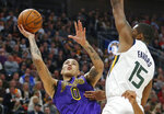 Los Angeles Lakers forward Kyle Kuzma (0) shoots as Utah Jazz forward Derrick Favors (15) defends during the first half of an NBA basketball game Friday, Jan. 11, 2019, in Salt Lake City. (AP Photo/Rick Bowmer)
