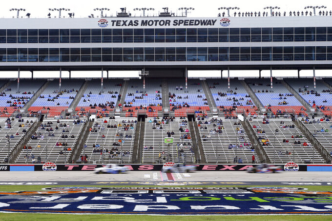 Fans watch a NASCAR Gander RV and Outdoors Truck Series auto race at Texas Motor Speedway in Fort Worth, Texas, Sunday Oct. 25, 2020. (AP Photo/Richard W. Rodriguez)