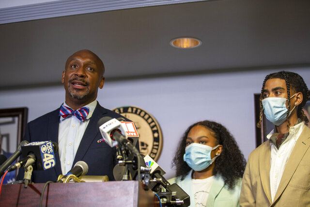 Attorney Mawuli Davis, left, speaks on behalf of Taniyah Pilgrim, center, and Messiah Young, right, during a press conference by the Fulton County District Attorney's Office in Atlanta, Monday, June 2, 2020. Six Atlanta police officers have been charged after a dramatic video showed authorities pulling the two young people from a car during protests over the death of George Floyd. (Alyssa Pointer/Atlanta Journal-Constitution via AP)