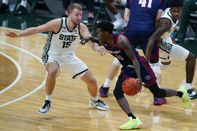 Detroit Mercy guard Antoine Davis (0) drives against Michigan State forward Thomas Kithier (15) during the first half of an NCAA college basketball game, Friday, Dec. 4, 2020, in East Lansing, Mich. (AP Photo/Carlos Osorio)