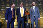 FILE - Clemson head coach Dabo Swinney, left, jokes with LSU head coach Ed Orgeron and Oklahoma head coach Lincoln Riley, right, as they pose with the College Football Championship trophy during a news conference ahead for the College Football playoffs in Atlanta, in this Thursday, Dec. 12, 2019, file photo. The College Football Playoff would expand from four to 12 teams, with six spots reserved for the highest ranked conference champions, under a proposal that will be considered next week by the league commissioners who manage the postseason system. A 12-team playoff would also include six at-large selections and no limit on how many teams can come from any one conference, a person familiar with announcement told The Associated Press on Thursday, June 10, 2021. The person spoke on condition of anonymity because the CFP has not yet released details. (AP Photo/John Bazemore, File)