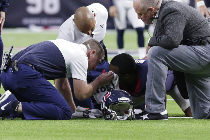Houston Texans quarterback Deshaun Watson, center, is attended to after he was injured during the second half of an NFL football game against the Oakland Raiders Sunday, Oct. 27, 2019, in Houston. (AP Photo/Michael Wyke)