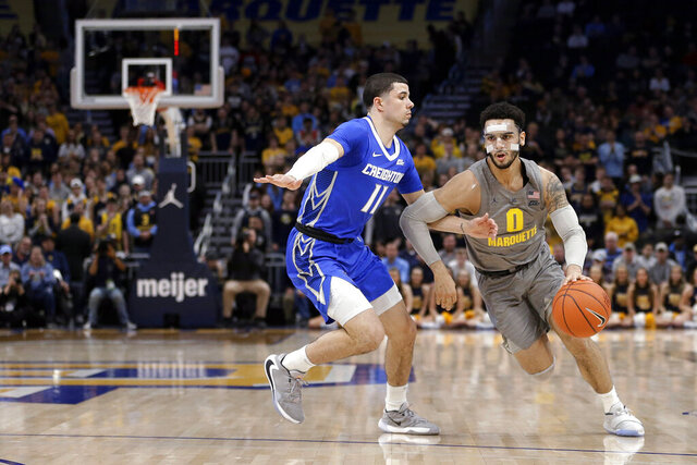 Marquette's Markus Howard (0) drives to the basket against Creighton's Marcus Zegarowski (11) during the first half of an NCAA college basketball game Tuesday, Feb. 18, 2020, in Milwaukee. (AP Photo/Aaron Gash)