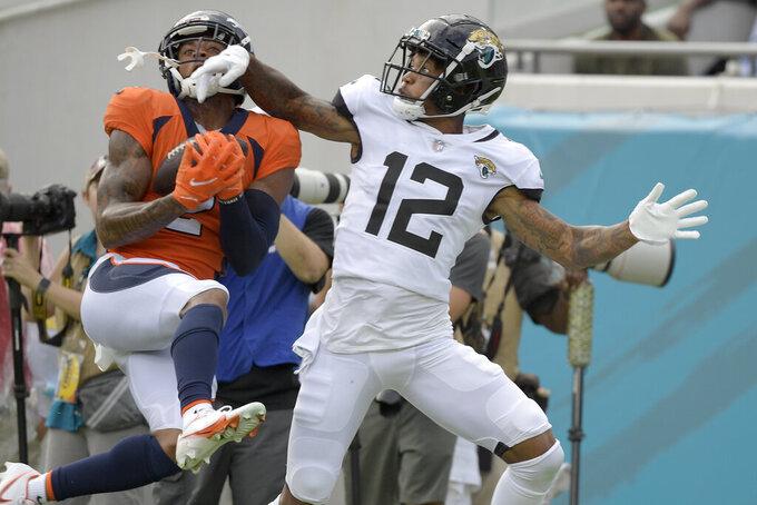 Denver Broncos cornerback Pat Surtain II, left, intercepts a pass intended for Jacksonville Jaguars wide receiver Tyron Johnson (12) during the second half of an NFL football game, Sunday, Sept. 19, 2021, in Jacksonville, Fla. (AP Photo/Phelan M. Ebenhack)