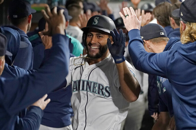 Seattle Mariners' Abraham Toro is greeted in the dugout after he hit a grand slam off Houston Astros relief pitcher Kendall Graveman during the eighth inning of a baseball game, Tuesday, Aug. 31, 2021, in Seattle. The Mariners won 4-0. (AP Photo/Ted S. Warren)