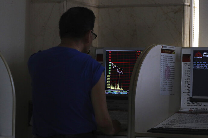 An investor monitors prices at a stock brokerage in Beijing on Tuesday, April 23, 2019. Asian stocks were mixed on Tuesday while oil prices soared to their highest level since October after the U.S. said it would soon impose sanctions on all buyers of Iranian oil. (AP Photo/Ng Han Guan)