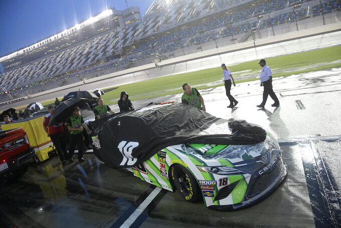 Crew members of Kyle Busch (18) push their car off pit road after a NASCAR Cup Series auto race was postponed to the next day at Daytona International Speedway, Saturday, July 6, 2019, in Daytona Beach, Fla. (AP Photo/Phelan M. Ebenhack)