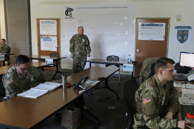Washington Army National Guard Col. Kevin McMahan, center, stands next to a map of confirmed positive cases and deaths attributed to the new coronavirus in Washington state as he observes activities in the operations room for the coordination of Washington National Guard troops and active duty U.S. Army soldiers working in Washington state in response to the new coronavirus outbreak, Tuesday, March 31, 2020, at Camp Murray, Wash. McMahan is the title 32 deputy commander with Joint Taskforce Steelhead, the coordinated effort between the Washington National Guard and a field hospital unit of U.S. Army soldiers from Colorado who are setting up a field hospital for non-coronavirus patients at the CenturyLink Field Events Center in Seattle. (AP Photo/Ted S. Warren)