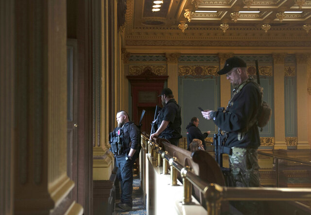 FILE - In this April 30, 2020, file photo, armed members of a militia group watch the protest outside while waiting for the Michigan Senate to vote at the Capitol in Lansing, Mich. Michigan has banned the open carry of guns in the state Capitol a week after an armed mob rioted in the U.S. Capitol and following an attempt to storm the statehouse last year. (Nicole Hester/MLive.com/Ann Arbor News via AP File)