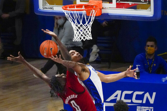 Pittsburgh's Justin Champagnie, right, shoots as North Carolina State's DJ Funderburk (0) defends during the second half of an NCAA college basketball game, Wednesday, Feb. 17, 2021, in Pittsburgh. North Carolina State won 74-73. (AP Photo/Keith Srakocic)