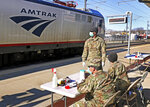 Members of the 1207th Rhode Island National Guard wait for disembarking passengers at the Amtrak station in Westerly, R.I., Friday, March 27, 2020, to inform passengers from New York of the 14-day quarantine restrictions if disembarking in Rhode Island ordered by Gov. Gina Raimondo. No passengers had disembarked at the time of the photo. (Harold Hanka/The Sun via AP)