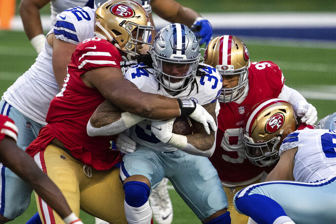 Dallas Cowboys' Rico Dowdle is tackled as he carries the ball against the San Francisco 49ers in the second quarter of an NFL football game Sunday, Dec. 20, 2020, in Arlington, Texas. (Yffy Yossifor/Star-Telegram via AP)
