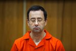 FILE - In this Feb. 5, 2018, file photo, Larry Nassar listens during his sentencing at Eaton County Circuit Court in Charlotte, Mich. From doping, to demonstrations to dirty officials, the Olympics have never lacked their share of off-the-field scandals and controversies that keep the Games in the headlines long after the torch goes out. Nassar's sexual abuse of hundreds of gymnasts in the U.S. opened a window into an abusive culture that permeates throughout the sport, and in all corners of the globe. (Cory Morse/The Grand Rapids Press via AP, File)