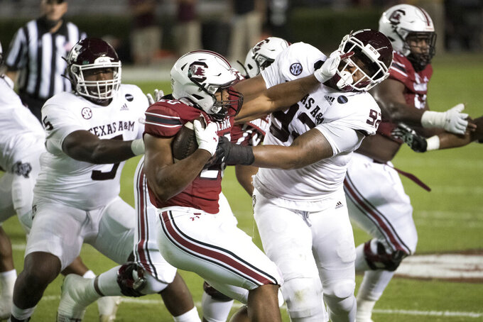 South Carolina running back Kevin Harris (20) stiff-arms Texas A&M defensive lineman Jayden Peevy (92) during the first half of an NCAA college football game Saturday, Nov. 7, 2020, in Columbia, S.C. (AP Photo/Sean Rayford)