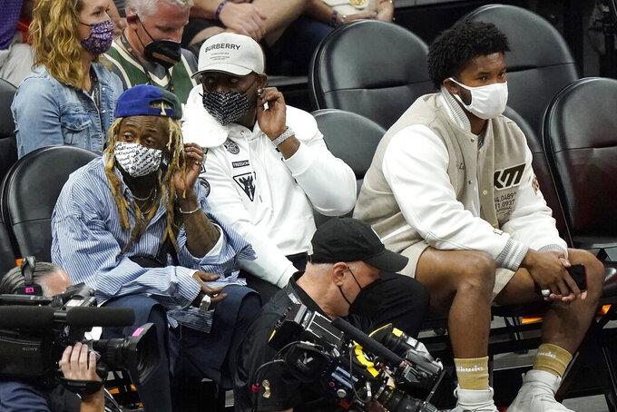 Musician Lil Wayne, left, and Arizona Cardinals quarterback Kyler Murray, right, watch Game 5 of basketball's NBA Finals between the Phoenix Suns and the Milwaukee Bucks, Saturday, July 17, 2021, in Phoenix. (AP Photo/Matt York)