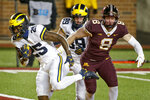 Michigan running back Hassan Haskins (25) rushes past tight end Carter Selzer (89) and Thomas Rush (8) for a touchdown in the second quarter of an NCAA college football game Saturday, Oct. 24, 2020, in Minneapolis. (AP Photo/Bruce Kluckhohn)