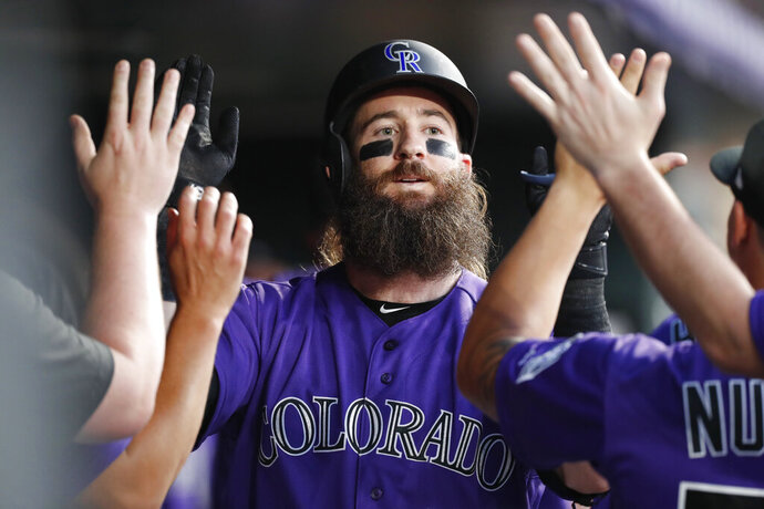 Colorado Rockies' Charlie Blackmon is congratulated as he returns to the dugout after hitting a solo home run off San Diego Padres starting pitcher Eric Lauer during the third inning of a baseball game Saturday, Sept. 14, 2019, in Denver. (AP Photo/David Zalubowski)