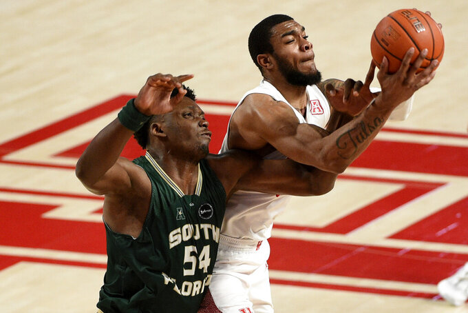 Houston forward Reggie Chaney, right, and South Florida center Russel Tchewa vie for a rebound during the second half of an NCAA college basketball game, Sunday, Feb. 28, 2021, in Houston. (AP Photo/Eric Christian Smith)