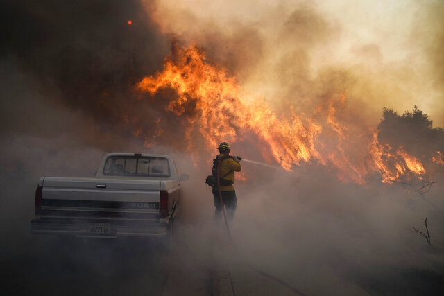 Firefighter Raymond Vasquez battles the Silverado Fire Monday, Oct. 26, 2020, in Irvine, Calif. A fast-moving wildfire forced evacuation orders for 60,000 people in Southern California on Monday as powerful winds across the state prompted power to be cut to hundreds of thousands to prevent utility equipment from sparking new blazes. (AP Photo/Jae C. Hong)