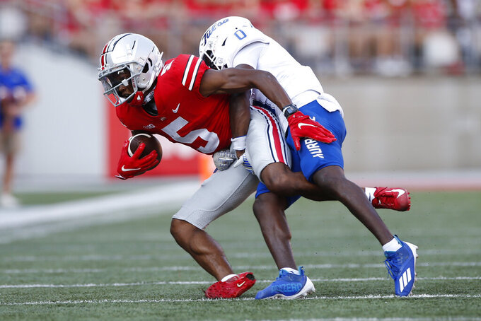 Tulsa defensive back Tyon Davis, right, tackles Ohio State receiver Garrett Wilson and during the first half of an NCAA college football game Saturday, Sept. 18, 2021, in Columbus, Ohio. (AP Photo/Jay LaPrete)