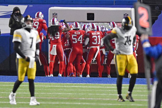Pittsburgh Steelers quarterback Ben Roethlisberger (7) and Chukwuma Okorafor (76) walk off the field as the Buffalo Bills defense celebrates a 51-yard interception returned for a touchdown during the first half of an NFL football game in Orchard Park, N.Y., Sunday, Dec. 13, 2020. (AP Photo/Adrian Kraus)
