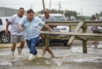 Louisiana Lt. Gov. Billy Nungesser, left center, helps move a wooden barricade to block a road where water was rising in Plaquemines Parish just south of New Orleans as Hurricane Barry makes landfall along the coast on Saturday, July 13, 2019. (Chris Granger/The Advocate via AP)