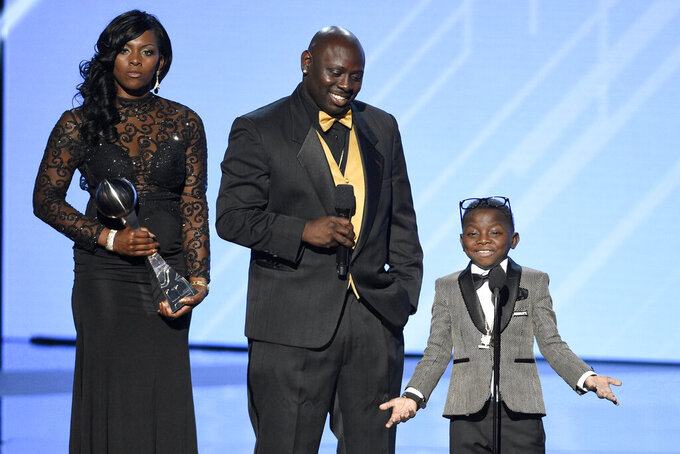 "FILE - In this Wednesday, July 12, 2017, file photo, New Orleans Saints super fan Jarrius ""J.J."" Robertson, right, accepts the Jimmy V perseverance award with his parents, from left, Patricia Hoyal and Jordy Robertson at the ESPYS at the Microsoft Theater on  in Los Angeles. Jordy Robertson, whose seriously ill son Jarrius gained fame in New Orleans for his devotion to the Saints football team, was sentenced to eight years in prison Tuesday, May 11, 2021, for drug trafficking and for fraudulently capitalizing on his son's illness with a phony charity. (Photo by Chris Pizzello/Invision/AP, File)"
