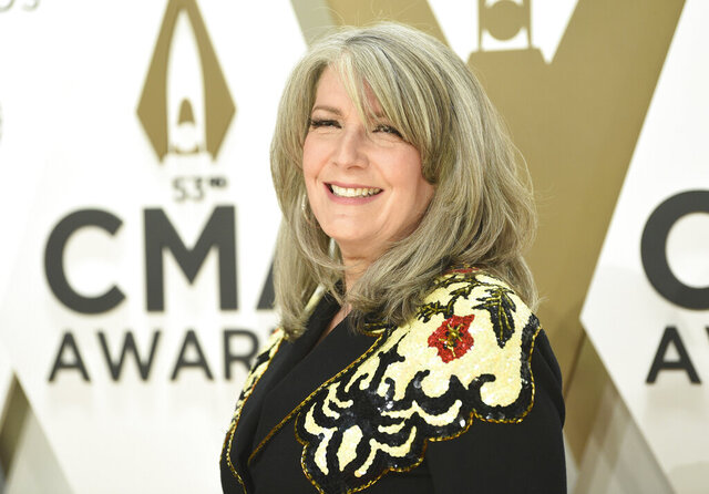 FILE - In this Nov. 13, 2019 file photo, Kathy Mattea arrives at the 53rd annual CMA Awards at Bridgestone Arena in Nashville, Tenn.  The country music star, who returned to West Virginia this Nov. 2020,  to host Mountain Stage for its second live, audience-free, streaming-only show at the Culture Center Theater in Charleston — bought a house with her husband, Jon Vezner, the year before.(Photo by Evan Agostini/Invision/AP, File)