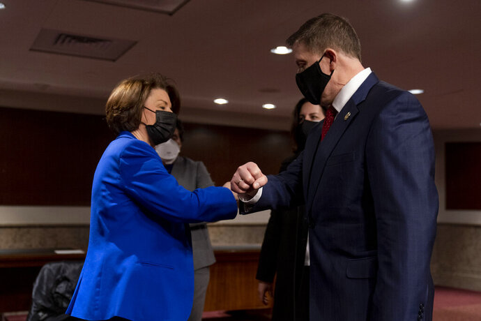 Chairwoman Sen. Amy Klobuchar, D-Minn., left, speaks with former U.S. Capitol Police Chief Steven Sund, right, following a Senate Homeland Security and Governmental Affairs & Senate Rules and Administration joint hearing on Capitol Hill, Washington, Tuesday, Feb. 23, 2021, to examine the January 6th attack on the Capitol. (AP Photo/Andrew Harnik, Pool)