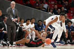 Connecticut center Josh Carlton, right, eyes a loose ball in front of Houston forward Fabian White Jr., center, as Connecticut head coach Dan Hurley looks on during the first half of an NCAA college basketball game Thursday, Jan. 23, 2020, in Houston. (AP Photo/Michael Wyke)