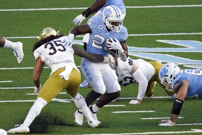 North Carolina running back Javonte Williams (25) runs the ball while Notre Dame linebacker Marist Liufau (35) tackles during the first half of an NCAA college football game in Chapel Hill, N.C., Friday, Nov. 27, 2020. (AP Photo/Gerry Broome)