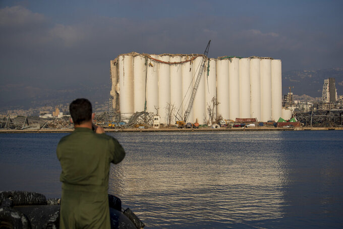 A Brazilian soldier takes a picture of a damaged silo that stands amid rubble and debris at the site of the Aug. 4 explosion that killed more than 170 people, injured thousands and caused widespread destruction, in Beirut, Lebanon, Thursday, Aug. 13, 2020. (AP Photo/Hassan Ammar)