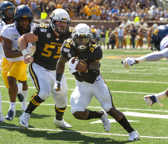 Missouri running back Larry Rountree III, right, scores a touchdown as he runs past teammate Trystan Colon-Castillo, center, and West Virginia safety Jovanni Stewart, left, during the first half of an NCAA college football game Saturday, Sept. 7, 2019, in Columbia, Mo. (AP Photo/L.G. Patterson)