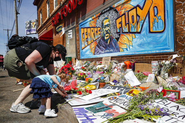 FILE - In this May 31, 2020 file photo, Jessica Knutson and her daughter Abigail, 3, place flowers at a memorial to George Floyd in Minneapolis. After a week of riots and looting over the loss of George Floyd, the Minneapolis black man who died after a police officer pressed his knee into his neck for more than eight minutes as he pleaded for air, parents are struggling to have the talk in this volatile moment, along with many others around race and racism. (AP Photo/John Minchillo, File)