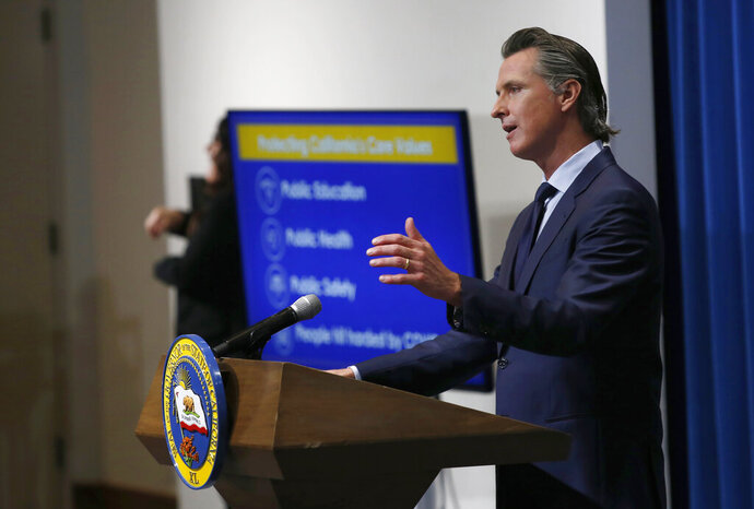 FILE - In this May 14, 2020, file photo, California Gov. Gavin Newsom discusses his revised 2020-2021 state budget during a news conference in Sacramento, Calif.  Spending cuts are compounding for schools and state programs, reserve funds are dwindling, and some governors have begun proposing new taxes and fees to shore up state finances shaken by the coronavirus pandemic. With Congress deadlocked over a new coronavirus relief package, many states haven't had the luxury of waiting to see whether more federal money will come their way.  (AP Photo/Rich Pedroncelli, Pool)