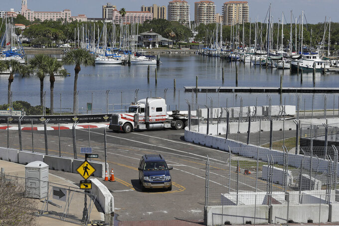 Workers begin to dismantle the track for the IndyCar Firestone Grand Prix of St. Petersburg auto race Monday, March 16, 2020, in St. Petersburg, Fla. Race organizers canceled the event to help curb the spread of the coronavirus. (AP Photo/Chris O'Meara)