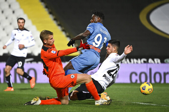 Atalanta's Duvan Zapata, center, is challenged by Spezia goalie Ivan Provedel and defender Martin Erlic during the Serie A soccer match between Spezia and Atalanta at the Dino Manuzzi stadium in Cesena, Italy, Saturday, Nov. 21, 2020. (Massimo Paolone/LaPresse via AP)