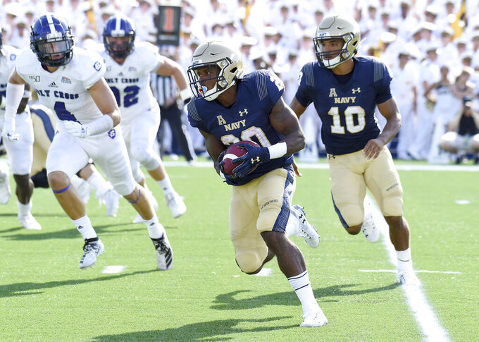 Navy slotback CJ Williams carries the ball after a pitch from quarterback Malcolm Perry   in the first quarter of an NCAA college football game against Holy Cross, Saturday, Aug. 31, 2019, in Annapolis, Md. (Paul W. Gillespie/Capital Gazette via AP)