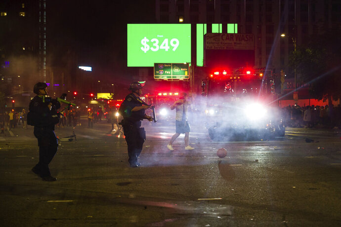 Los Angeles police officers attempt to disperse rowdy fans in the street, Sunday, Oct. 11, 2020, in Los Angeles, after the Los Angeles Lakers defeated the Miami Heat in Game 6 of basketball's NBA Finals to win the championship. (AP Photo/Jintak Han)