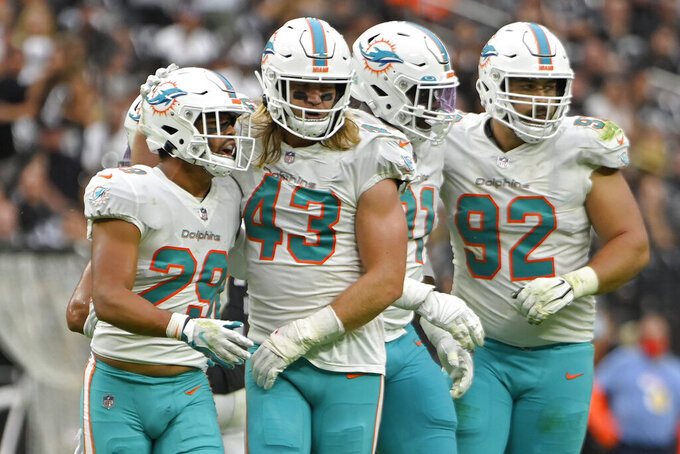 Miami Dolphins defensive back Brandon Jones (29) and outside linebacker Andrew Van Ginkel (43) celebrate after a sack play against the Las Vegas Raiders during the first half of an NFL football game, Sunday, Sept. 26, 2021, in Las Vegas. (AP Photo/David Becker)