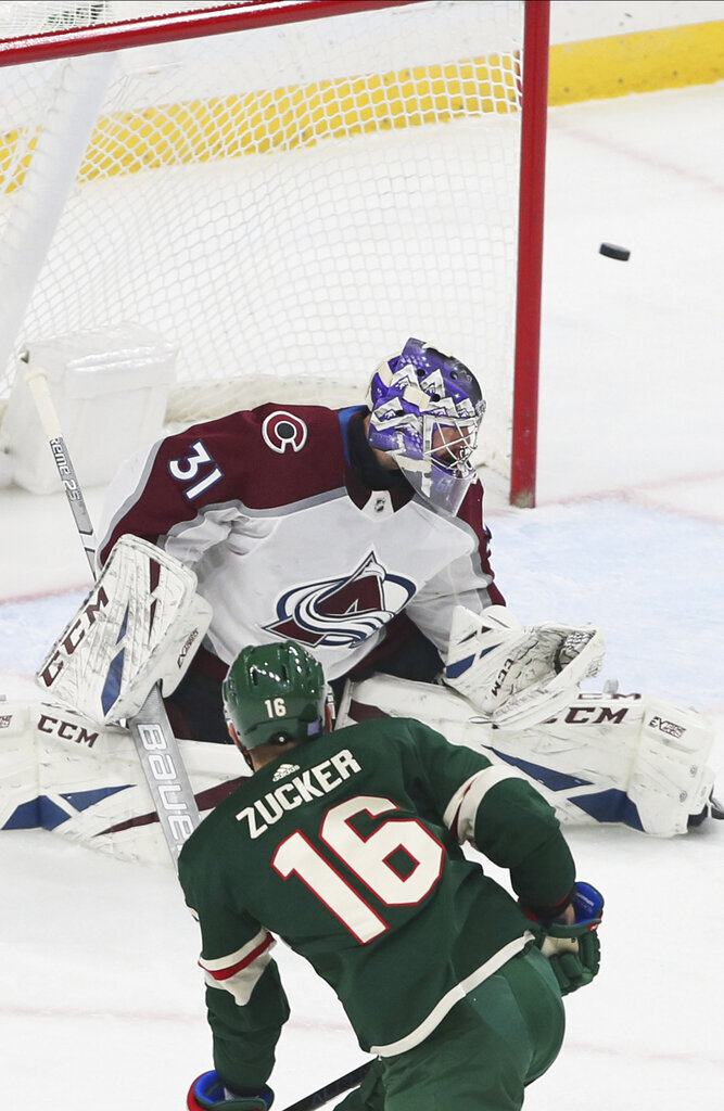 A shot by Minnesota Wild's Jason Zucker, left, goes wide of Colorado Avalanche's goalie Philipp Grubauer of Germany in the first period of an NHL hockey game Thursday, Nov. 21, 2019, in St. Paul, Minn. (AP Photo/Jim Mone)