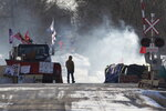 A protester stands beside smoke at the closed train tracks in Tyendinaga Mohawk Territory near Belleville, Ontario on Thursday Feb. 20, 2020, as demonstrators protest in solidarity with the Wet'suwet'en hereditary chiefs opposed to the LNG pipeline in northern British Columbia. (Lars Hagberg/The Canadian Press via AP)
