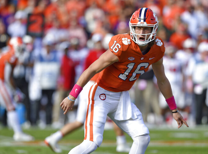 FILE - In this Oct. 20, 2018, file photo, Clemson quarterback Trevor Lawrence calls a play during the first half of the team's NCAA college football game against North Carolina State in Clemson, S.C. Clemson and Notre Dame weren't even a month into this season when both made unexpected quarterback switches. The Tigers and Fighting Irish were undefeated with senior quarterbacks who had won a lot of games, and neither of those starters was even injured. Still, the coaches for both teams decided to make a change then--and are still without a loss going for a national title. After playing behind Kelly Bryant in each of Clemson's first four games, Lawrence was named the starter before the Sept. 29 game at Wake Forest. (AP Photo/Richard Shiro, File)