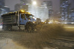 A Streets and Sanitation snow plow works East Wacker Drive during a snowstorm Friday, Jan. 17, 2020, in Chicago.  A winter storm that has already caused trouble at airports in Chicago and Kansas City was expected to bring blizzard conditions to the Plains and Midwest on Saturday and could dump up to a foot of snow in parts of the Northeast on Sunday.  (John J. Kim /Chicago Tribune via AP)