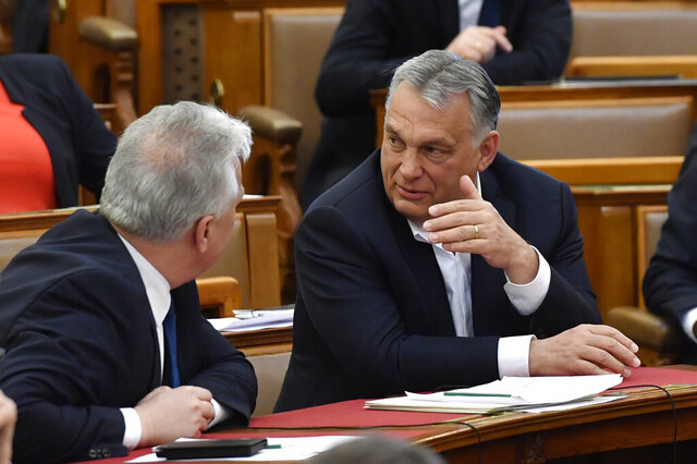 Hungarian Prime Minister Viktor Orban, right, chats with his deputy Zsolt Semjen during a plenary session of the Parliament in Budapest, Hungary, Budapest, Hungary, Monday, March 30, 2020. Hungary's parliament on Monday approved a bill giving Prime Minister Viktor Orban's government extraordinary powers during the coronavirus pandemic, without setting an end date for their expiration.  The bill was approved by Orban's Fidesz party and other government supporters by 137 votes in favor to 53 against. (Zoltan Mathe/MTI via AP)