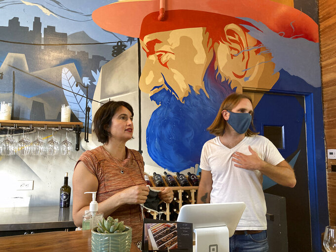 """In this Sunday, May 2, 2021, photo, Angeleno Wine Company owners Amy Luftig Viste, left, and Jasper Dickson pose for a picture in downtown Los Angeles. When Angeleno Wine Co. reopened its tasting room to the public, Luftig Viste teared up seeing old friends reunited for the first time since the pandemic had shuttered so many businesses that it left major cities looking like ghost towns. """"It felt like the winery had come alive again,"""" Luftig Viste said Sunday, the day after it officially reopened after being closed all but two weeks over the past 13 months. (AP Photo/Brian Melley)"""