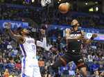 Oklahoma City Thunder forward Paul George, left, tries to get to a rebound before Miami Heat forward Derrick Jones Jr. in the first half of an NBA basketball game , Monday, March 18, 2019, in Oklahoma City. (AP Photo/Kyle Phillips)