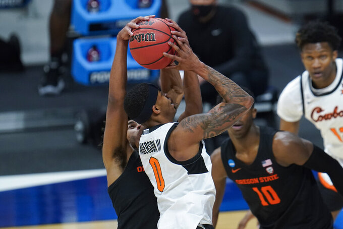 Oregon State guard Ethan Thompson (5) blocks a Oklahoma State guard Avery Anderson III (0) shot during the first half of a men's college basketball game in the second round of the NCAA tournament at Hinkle Fieldhouse in Indianapolis, Sunday, March 21, 2021. (AP Photo/Paul Sancya)